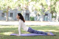 Donna atletica che fa yoga nel parco di mattina di estate Tempo per yoga Bella signora in abiti sportivi sta sorridendo mentre fa Fotografie Stock Libere da Diritti