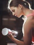 Donna atletica che pompa sui muscules con le teste di legno Immagini Stock