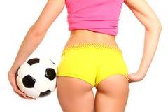 Donna atletica che posa con un pallone da calcio su un fondo bianco, Fotografie Stock