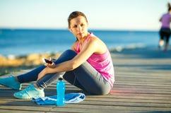 Donna atletica che riposa dopo avere corso all'addestramento di mattina vicino Immagine Stock