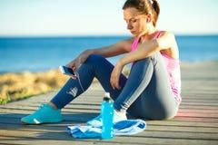 Donna atletica che riposa dopo avere corso all'addestramento di mattina vicino Fotografia Stock