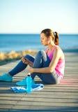 Donna atletica che riposa dopo avere corso all'addestramento di mattina vicino Immagine Stock Libera da Diritti