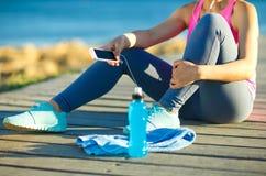 Donna atletica che riposa dopo avere corso all'addestramento di mattina vicino Fotografia Stock Libera da Diritti
