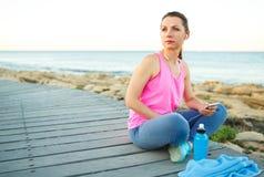 Donna atletica che riposa dopo avere corso all'addestramento di mattina vicino Immagini Stock