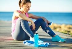 Donna atletica che riposa dopo avere corso all'addestramento di mattina vicino Immagini Stock Libere da Diritti