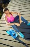Donna atletica che riposa dopo avere corso all'addestramento di mattina vicino Fotografie Stock