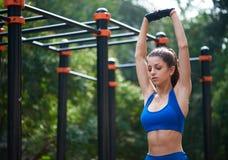 Donna atletica che si scalda prima del suo allenamento di mattina alla zona all'aperto del workot Concetto sano di stile di vita Fotografie Stock Libere da Diritti