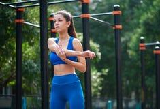 Donna atletica che si scalda prima del suo allenamento di mattina alla zona all'aperto del workot Concetto sano di stile di vita Fotografia Stock Libera da Diritti