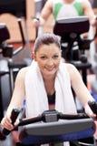 Donna atletica che utilizza una bicicletta in un centro sportivo Fotografia Stock
