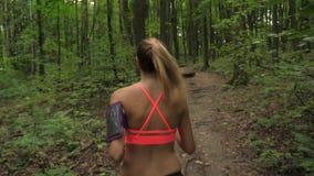Donna atletica con funzionamento lungo dei capelli su una pista, sugli sport e sulla ricreazione della foresta video d archivio