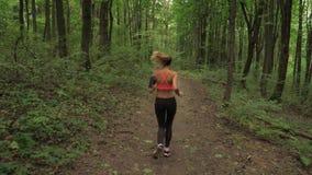 Donna atletica con le cuffie che corre su una pista, sugli sport e sulla ricreazione della foresta video d archivio