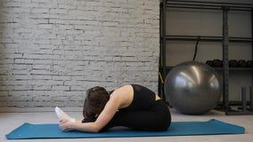 Donna atletica della stuoia di yoga giovane che allunga anca, muscoli del tendine del ginocchio, muscoli della gamba all'interno  video d archivio