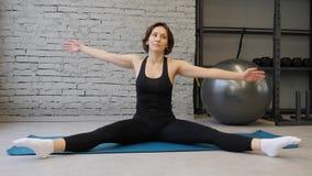 Donna atletica della stuoia di yoga giovane che allunga anca, muscoli del tendine del ginocchio, muscoli della gamba all'interno  stock footage