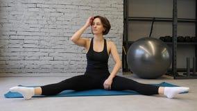 Donna atletica della stuoia di yoga giovane che allunga anca, muscoli del tendine del ginocchio, muscoli della gamba all'interno  archivi video