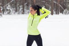 Donna atletica di misura che si scalda nell'inverno della foresta Immagine Stock