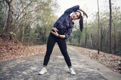 Donna atletica scaldarsi di Asia e giovane exercisi dell'atleta femminile Immagini Stock