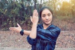 Donna atletica scaldarsi di Asia e giovane exercisi dell'atleta femminile Fotografie Stock