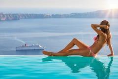 Donna atletica su uno stagno di infinito in Santorini, Grecia fotografia stock libera da diritti