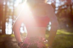 Donna atletica in una foresta, orologio astuto d'uso di misura anonima attraente, prendente una rottura dall'allenamento intenso immagine stock libera da diritti