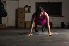 Donna attiva che fa spinta-UPS in una palestra Fotografia Stock