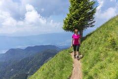Donna attiva che fa un'escursione nelle montagne sopra la valle immagine stock