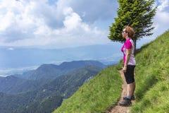Donna attiva che fa un'escursione nelle montagne sopra la valle immagini stock