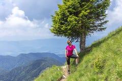 Donna attiva che fa un'escursione nelle montagne sopra la valle fotografia stock libera da diritti