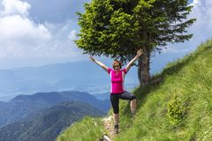 Donna attiva che fa un'escursione nelle montagne sopra la valle immagine stock libera da diritti