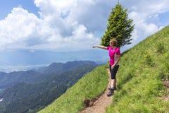 Donna attiva che fa un'escursione nelle montagne sopra la valle immagini stock libere da diritti