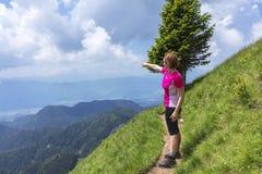 Donna attiva che fa un'escursione nelle montagne sopra la valle fotografie stock