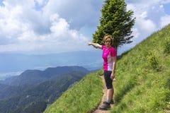 Donna attiva che fa un'escursione nelle montagne sopra la valle fotografia stock