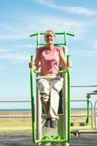 Donna attiva che si esercita sull'aumento della gamba all'aperto Immagini Stock Libere da Diritti