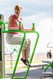 Donna attiva che si esercita sull'aumento della gamba all'aperto Immagine Stock