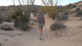 Donna attiva con i bastoni di trekking che fanno un'escursione nel parco Joshua Tree del deserto del Mojave Immagine Stock