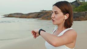 Donna attiva di stile di vita che guarda l'orologio astuto dello smartwatch di tecnologia Macro fine del primo piano sul touch sc stock footage
