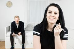 Donna attiva sorridente che lavora allo scrittorio ed all'uomo elegante che aspettano nei precedenti fotografia stock libera da diritti
