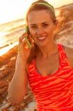 Donna attiva sorridente sulla spiaggia che parla sul telefono cellulare Fotografia Stock