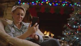 Donna attraente adulta che utilizza smartphone per la chiacchierata nella notte di natale davanti al camino archivi video