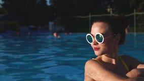 Donna attraente alla moda in costume da bagno ed occhiali da sole gialli nella piscina archivi video