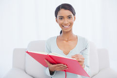 Donna attraente allegra che si siede sulla scrittura accogliente del sofà Immagini Stock