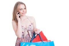 Donna attraente allegra con i sacchetti della spesa che parla sullo smartphone fotografia stock libera da diritti