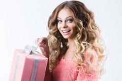 Donna attraente allegra con il regalo di apertura su bianco Immagine Stock
