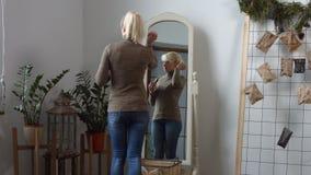 Donna attraente allo specchio che applica rossetto rosso archivi video