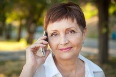 Donna attraente 50 anni con un telefono cellulare Immagine Stock Libera da Diritti