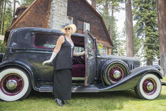 Donna attraente in attrezzatura di anni venti vicino all'oggetto d'antiquariato A Fotografia Stock