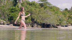 Donna attraente in bikini che entra in acqua di mare cristallina sulla spiaggia di paradiso Bella donna che cammina all'acqua del video d archivio