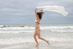 Donna attraente castana spensierata sulla spiaggia Immagini Stock