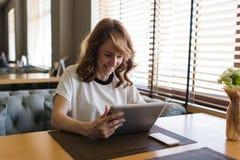 Donna attraente caucasica che ha video conversazione facendo uso del cuscinetto di tocco Fotografie Stock