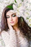 Donna attraente caucasica con gli occhi chiusi sulla parete dei gigli bianchi Fotografia Stock