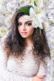 Donna attraente caucasica con gli occhi chiusi sulla parete dei gigli bianchi Immagini Stock Libere da Diritti